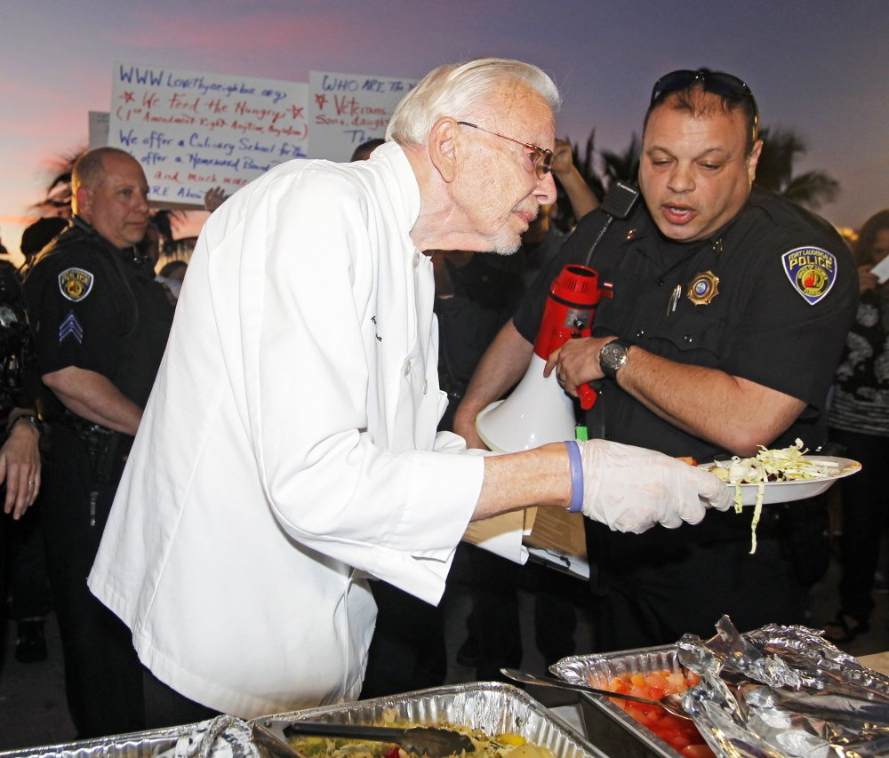 Arnold Abbott, president of Love Thy Neighbor, is told by Sgt. Al Lerner that he is breaking the law, as he serves food to the hungry in Fort Lauderdale on Nov. 12.