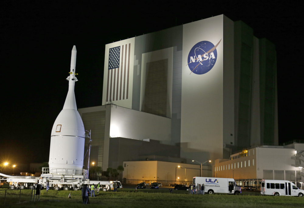The Orion Spacecraft moves by the Vehicle Assembly Building in  early November on its 22-mile journey from the Launch Abort System Facility at the Kennedy Space Center to Space Launch Complex 37B at the Cape Canaveral Air Force Station in Cape Canaveral, Fla.