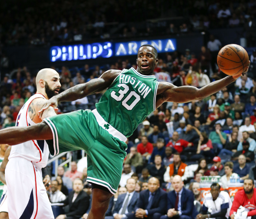 Boston Celtics forward Brandon Bass keeps the ball in bounds against Atlanta Hawks forward Pero Antic in the first half of Tuesday night's game in Atlanta, another loss for the 4-11 Celtics.