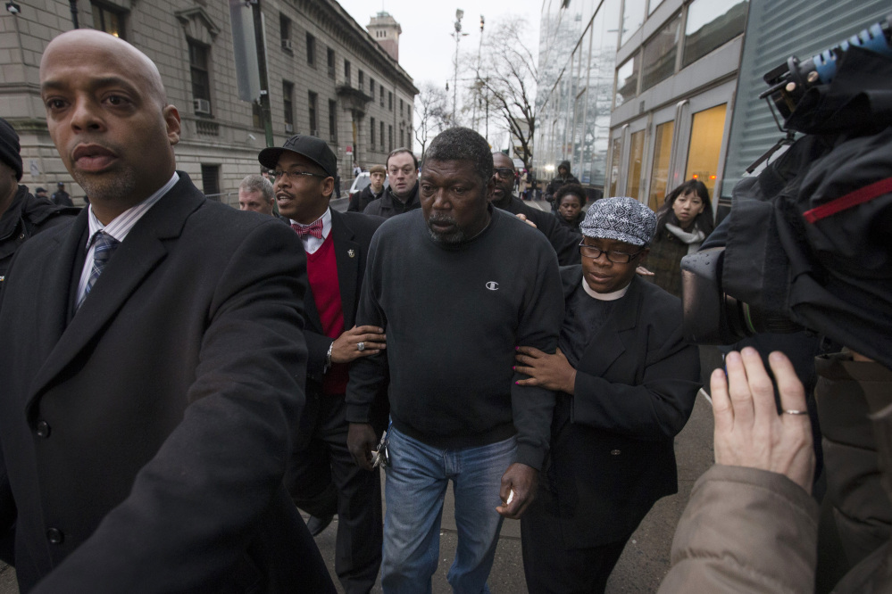 Benjamin Carr, the stepfather of Eric Garner, leaves the district attorney's office Wednesday after a grand jury's decision not to indict a New York police officer who was involved in Garner's death. A video shot by an onlooker and widely viewed on the Internet showed Garner telling officers to leave him alone as they tried to arrest him. The city medical examiner ruled Garner's death a homicide and found that a chokehold contributed to it.