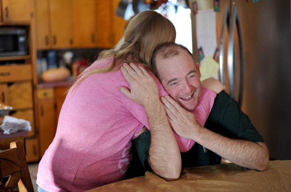 "Scott Greaney gets a hug from daughter Emily at the family dining room table before the Thanksgiving feast, the family's first ""real meal"" in a week."