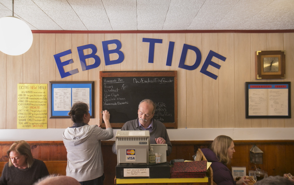 Peter Gilchrist, above, adjusts the cash register Thursday at the Ebb Tide restaurant in Boothbay Harbor while waitress Rose Marie Hodgdon wipes one of the specials off the menu board. Gilchrist and his wife, Nancy, closed the restaurant Thursday, exactly 40 years after they signed the papers to buy it.