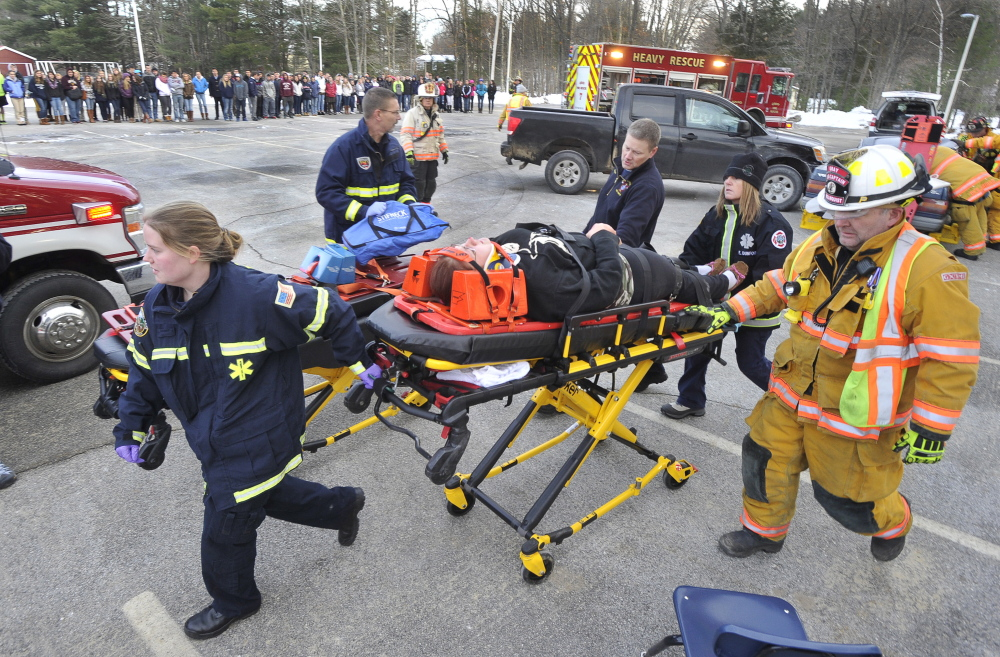 During a mock crash demonstration at Gray-New Gloucester High School on Friday, Gray Fire and Rescue personnel transport senior Tamica McNally as part of an effort to show students what can happen when texting while driving.