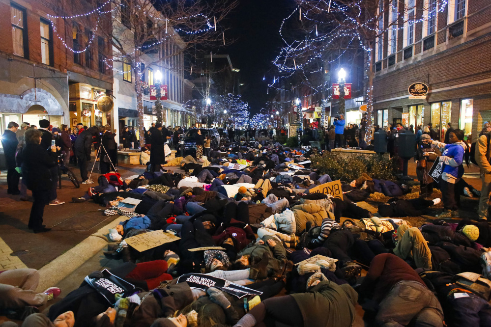 Hundreds of protestors have a die-in during the Kalamazoo Art Walk during a protest in downtown Kalamazoo, Mich. on Friday, Dec. 5, 2014 against the non indictments of the police officers involved in the deaths of Michael Brown in Ferguson, Mo. and Eric Garner in New York City.