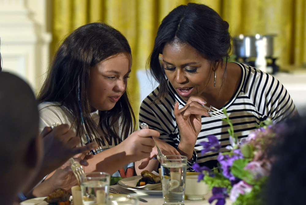 First lady Michelle Obama and a student confer as they eat lunch in the East Room of the White House in October, following the annual fall harvest of the White House Kitchen Garden. Some Republicans want to temporarily halt healthier school meal standards.