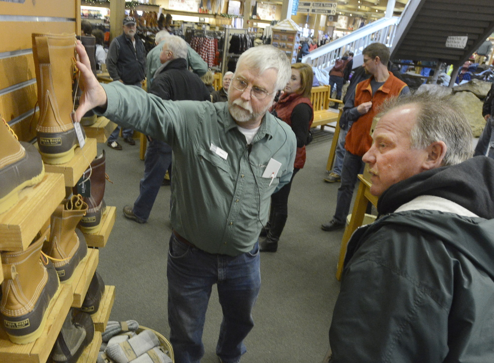 Steve James of L.L. Bean helps customer Barry Robichaud select a pair of Bean boots at the company's retail store in Freeport on Thursday.