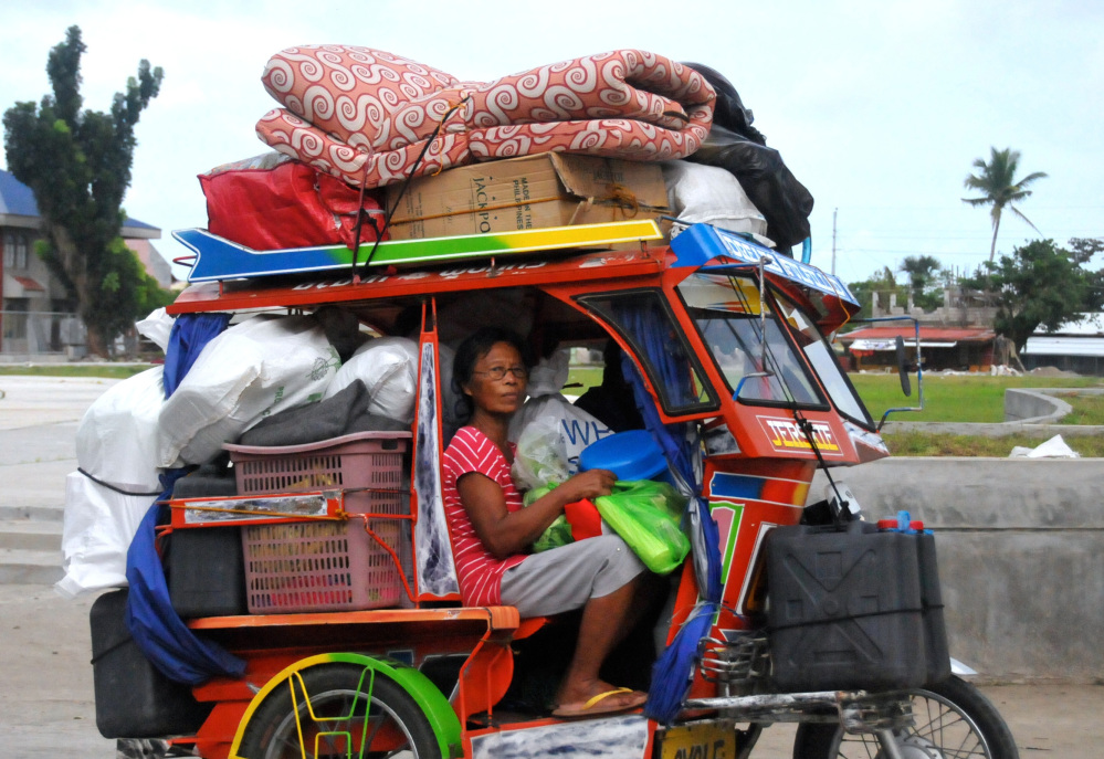 Typhoon survivors, some of whom are still living in tents, evacuate to safer grounds with their belongings at Tanauan township, Leyte province, in central Philippines on Thursday.