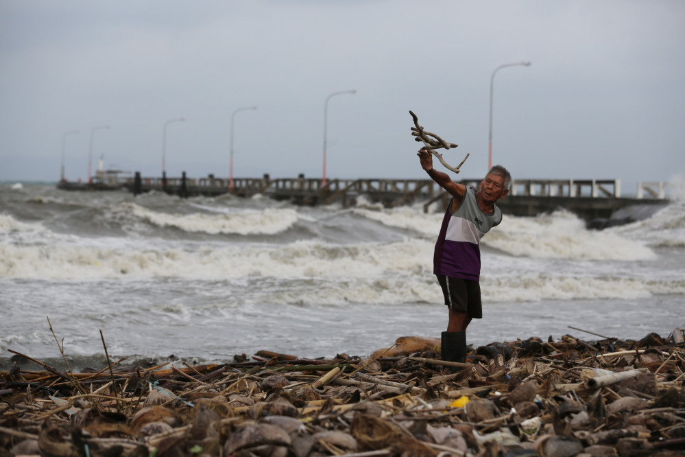A man throws wood along the shore as strong waves from Typhoon Hagupit hit Atimonan, Quezon province, eastern Philippines, Saturday. Haunted by Typhoon Haiyan's massive devastation last year, more than 600,000 people fled Philippine villages and the military went on full alert Saturday to brace for a powerful storm only hours away from the country's eastern coast.