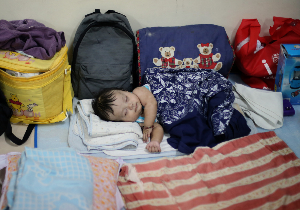 Filipino Jonrey Pawang sleeps beside his family's belongings as they take refuge at a school used as an evacuation center,  in Legazpi in the eastern Philippines on Saturday.