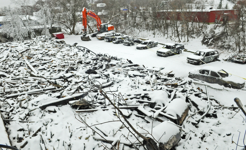 Snow covers the ruins of 36 Northern Ave. in Augusta and also blankets the burned cars parked behind it on Saturday.
