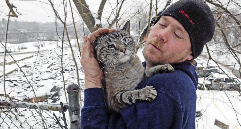 Dereck Oltz found this cat Saturday in woods near the charred remains of an Augusta apartment building that burned down on Friday. Oltz's mother, who lived in the building, said the cat belongs to a former neighbor.