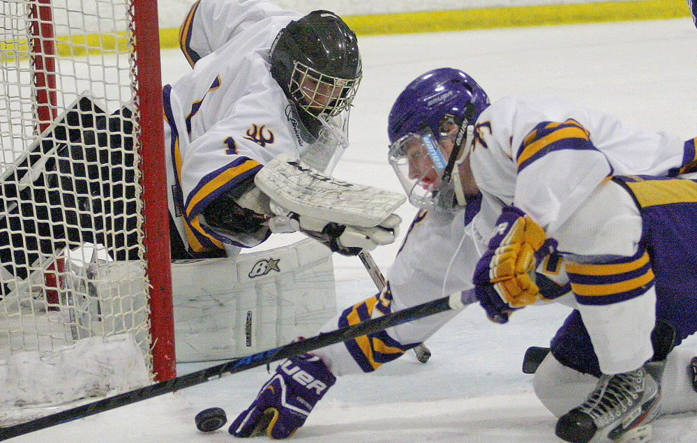 Cheverus goalie Kyle Severance and teammate James Kane try to keep the puck out of the net Saturday in a hockey season opener against Lewiston at Portland Ice Arena. Severance made 36 saves in a 3-2 overtime victory.