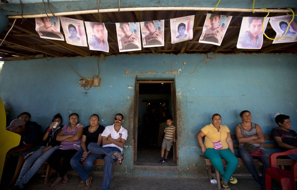 People gather outside of the home of Alexander Mora, one of 43 college students missing since September whose charred remains have now been positively identified among those found near a garbage dump in the town of El Pericon, Mexico.