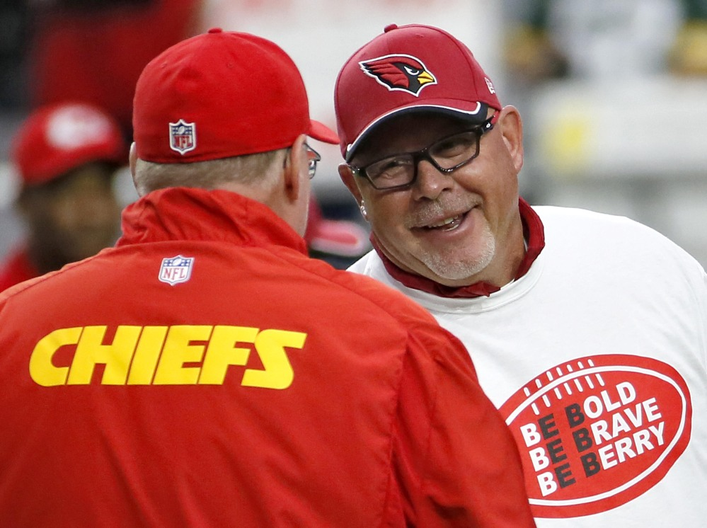 Arizona Cardinals coach Bruce Arians, right, wearing an Eric Berry T-shirt, greets Kansas City Chiefs coach Andy Reid before the teams' game Sunday in Glendale, Ariz.