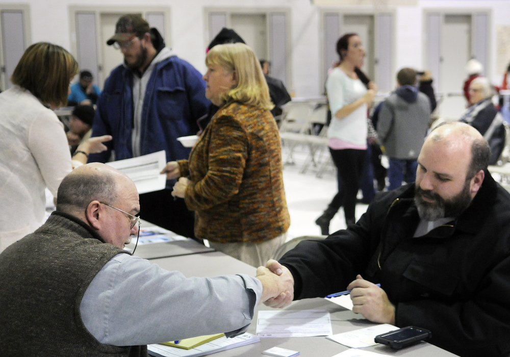 Arthur Gagne, right, shakes hands with Ronald Lachapelle Monday after filling out a rental application for C.B. Mattson's apartments during an event in Augusta to find services and housing for victims of the fire that destroyed an apartment building on Northern Avenue last week. Lachapelle is the administrator at C.B. Mattson, a statewide property management firm with offices in Farmingdale.
