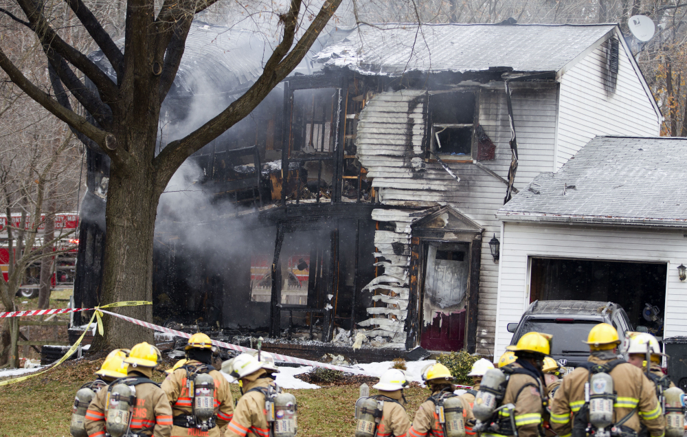Montgomery County, Md., firefighters stand outside a house where a small private jet crashed in Gaithersburg, Md., Monday.