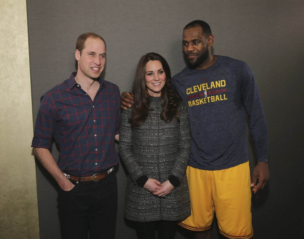 """Britain's Prince William, left, and Kate, Duchess of Cambridge, pose with LeBron James after Monday's game between the Cleveland Cavaliers in New York. Britain's Daily Mirror wrote, """"James raised more than a few eyebrows when he got up close with Kate, still dressed in a soggy sweater."""""""