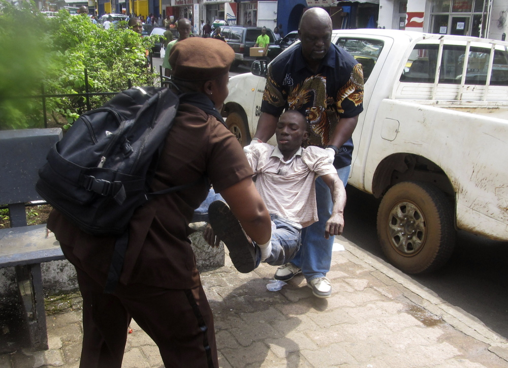 A man is carried away to be tested for Ebola after collapsing on a street in Monrovia, Liberia, on Tuesday. Sierra Leone is seeing an alarming spike in deaths from Ebola.