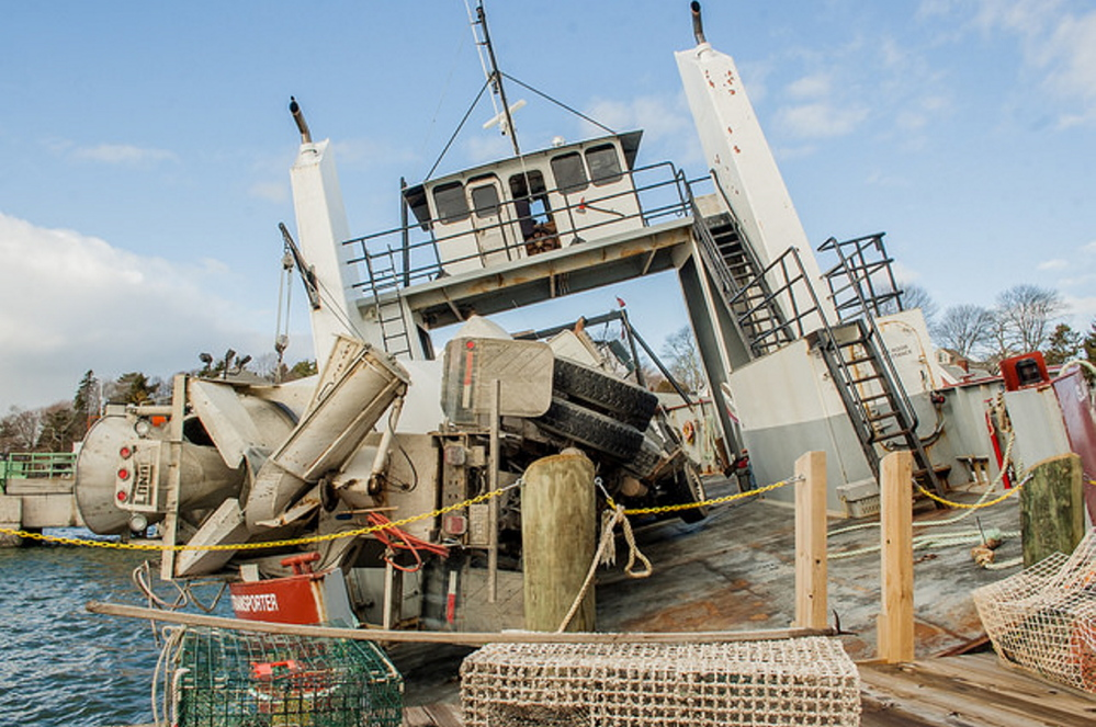 """Two heavy trucks lie against the port rail of the Island Transporter at a pier in North Haven on Thursday. """"They were lucky they didn't roll over and all drown,"""" North Haven Harbormaster Foy Brown said."""