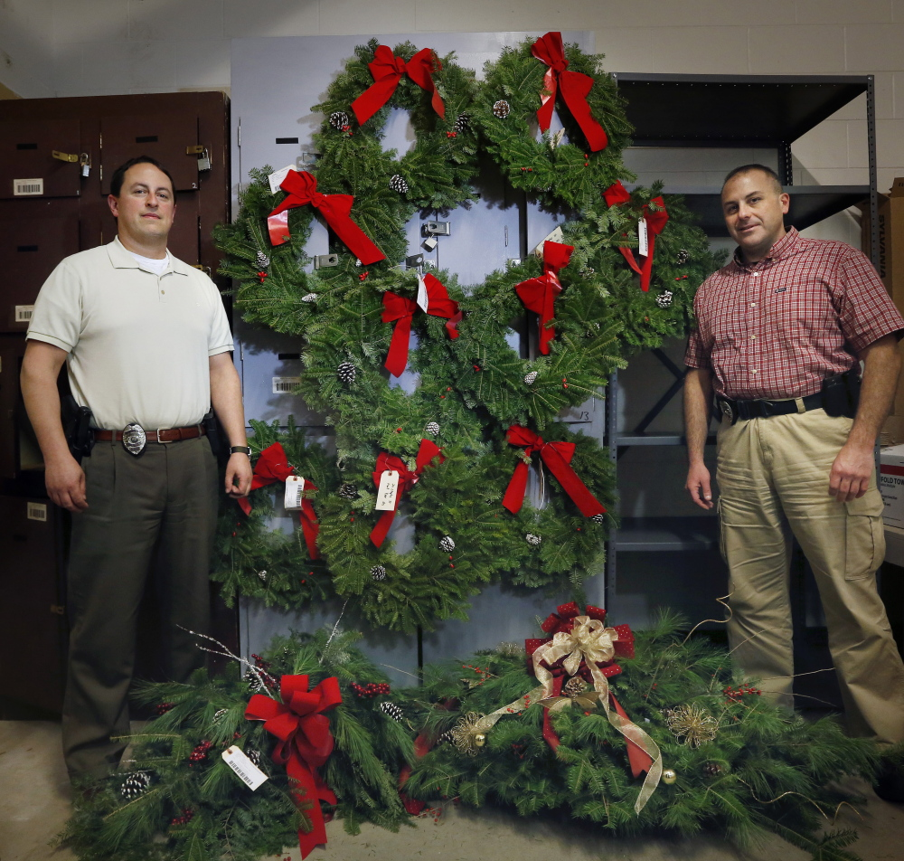 SACO, ME - DECEMBER 12:  Saco police detectives Jeffrey Cook, left, and Daryen Granata pose with the nine wreaths and two large holiday bouquets that were stolen from graves at Laurel Hill Cemetery. Today an Old Orchard Beach woman turned herself in after a warrant was put out for her arrest. Jeffrey Holland, deputy chief of police, joked that the department has a pleasant holiday smell to it now. (Photo by Derek Davis/Staff Photographer)