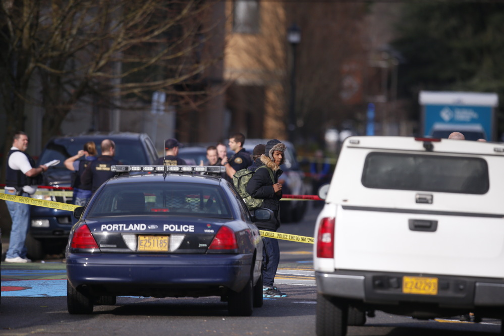 Police gather where a shooting occurred near Rosemary Anderson High School in Portland, Ore., on Friday.