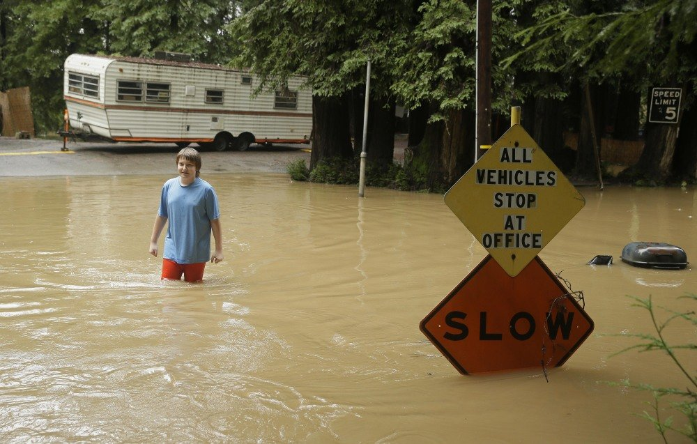 Andrew Waxman-Wright makes his way through floodwaters in Forestville, Calif. While the sun came out Friday, a storm's effects lingered in Northern California. The storm knocked out power to as many as 276,000 customers.