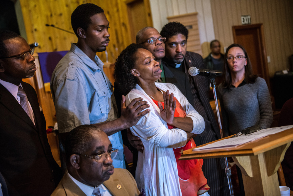 Claudia Lacy, center, cries as she thanks the people who showed up Dec. 1 at the First Baptist Church in Bladenboro, N.C., to hear the Rev. Dr. William Barber II, president of the North Carolina State Conference of the NAACP, talk about the investigation of her son's death. Lennon Lacy, 17, was found hanging from a swing set in the middle of a trailer park in late August.