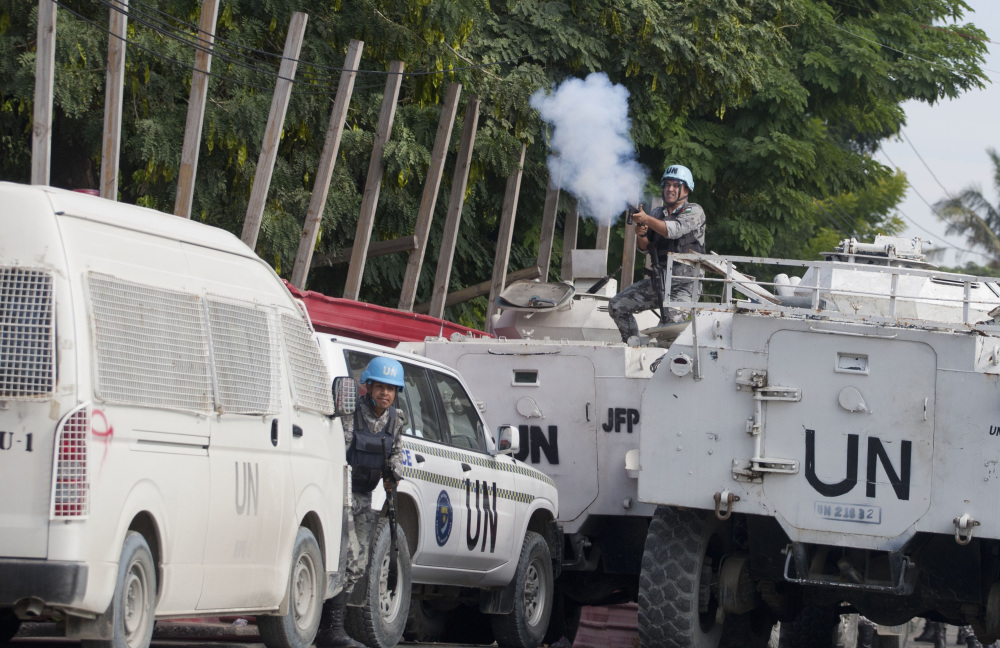 A Jordanian soldier from the U.N. peacekeeping force in Port-au-Prince, Haiti, fires tear gas at protesters demanding new government leadership on Friday. The protest occurred hours before President Michel Martelly discussed a report calling for a new consensus government.