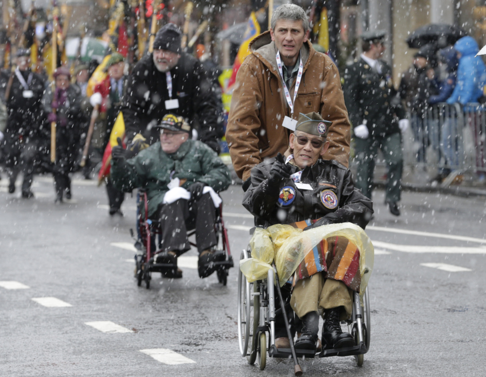 U.S. WWII veteran Bob Izumy of the 101st AB 506, participates in a parade during the 70th anniversary of the Battle of the Bulge in Bastogne, Belgium, Saturday.