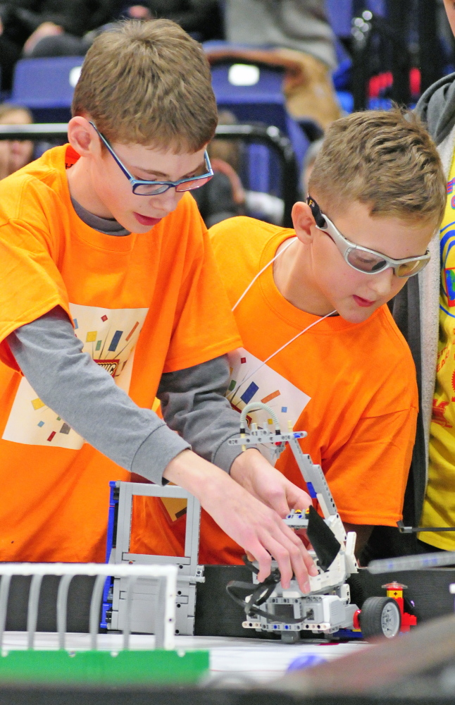 Trafton Gray, left, and Forest Holbrook set up the TechnicFreaks' robot on Saturday in the Augusta Civic Center. The TechnicFreaks are the first team from Hall-Dale schools in Hallowell to test their robotics in the Maine FIRST LEGO League Championship.