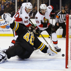 Ottawa's Alex Chiasson, center, and Mika Zibanejad, right, chase a puck in the crease behind Bruins goalie Tuukka Rask during the first period of Saturday's game in Boston. The Senators won 3-2 on Bobby Ryan's shootout goal.