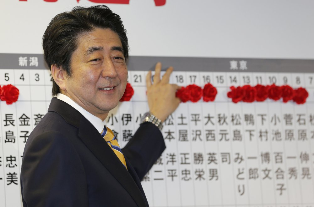 Japanese Prime Minister Shinzo Abe, leader of the Liberal Democratic Party, smiles as he places a red rosette on the name of his Liberal Democratic Party's winning candidate during ballot counting for the lower house elections at the party headquarters in Tokyo on Sunday.