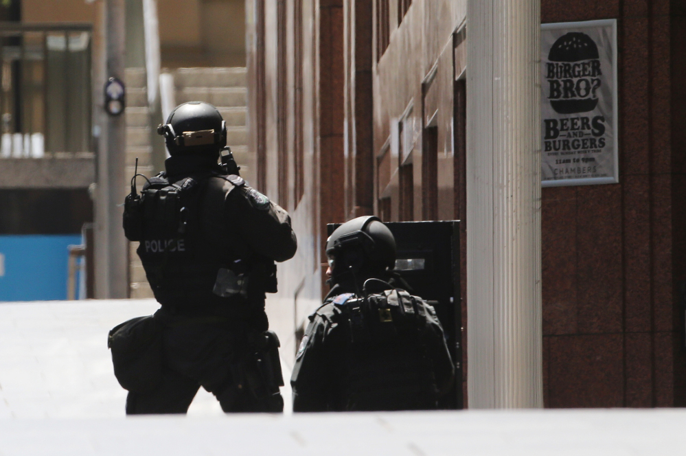 Police stand at the ready close to a cafe under siege in Martin Place in the central business district of Sydney, Australia, Monday. New South Wales state police would not say what was happening inside the cafe or whether hostages were being held. But television footage shot through the cafe's windows showed several people with their arms in the air.
