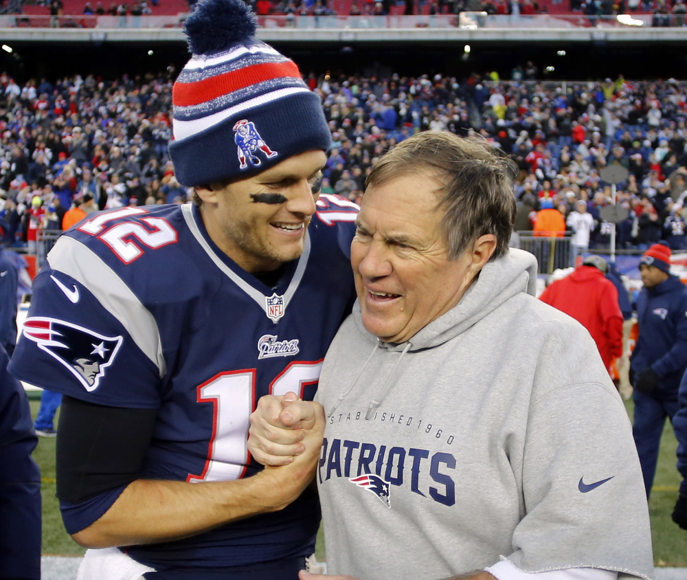 Tom Brady, left, and Bill Belichick celebrate after the Patriots' 41-13 win over Miami that gave New England its 11th AFC East title in 12 seasons. Reuters/Winslow Townson