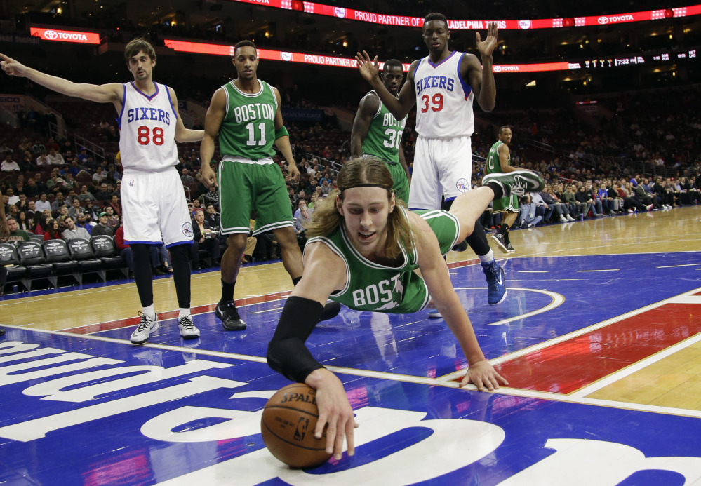 The Boston Celtics' Kelly Olynyk dives for a loose ball during the first half of Monday night's game against the Philadelphia 76ers. He scored a career-high 30 points in the Celtics' win.