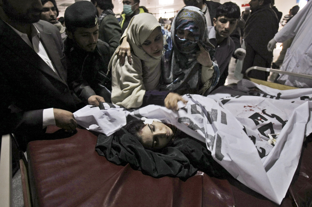 Relatives of a victim of a Taliban attack in a school, mourn over her lifeless body at a hospital in Peshawar, Pakistan, Tuesday.