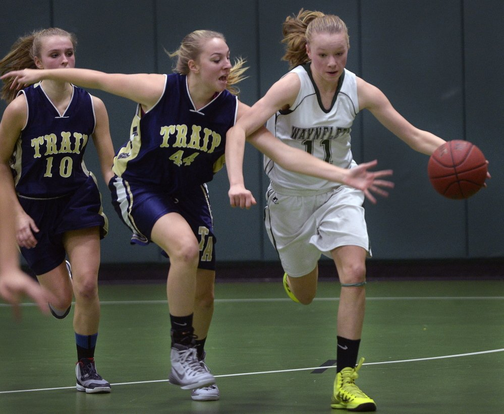 Waynflete's Lydia Giguere dribbles away from Traip Academy's Marina Casey in Tuesday night's girls' basketball game in Portland. Giguere had nine points in Waynflete's 63-32 win.