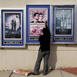 "A poster for the ""The Interview"" is taken down by a worker Wednesday at a Carmike Cinemas theater in Atlanta. Georgia-based Carmike Cinemas and other chains canceled showings of the film in response to threats, before Sony Pictures Entertainment canceled the film's Christmas release."