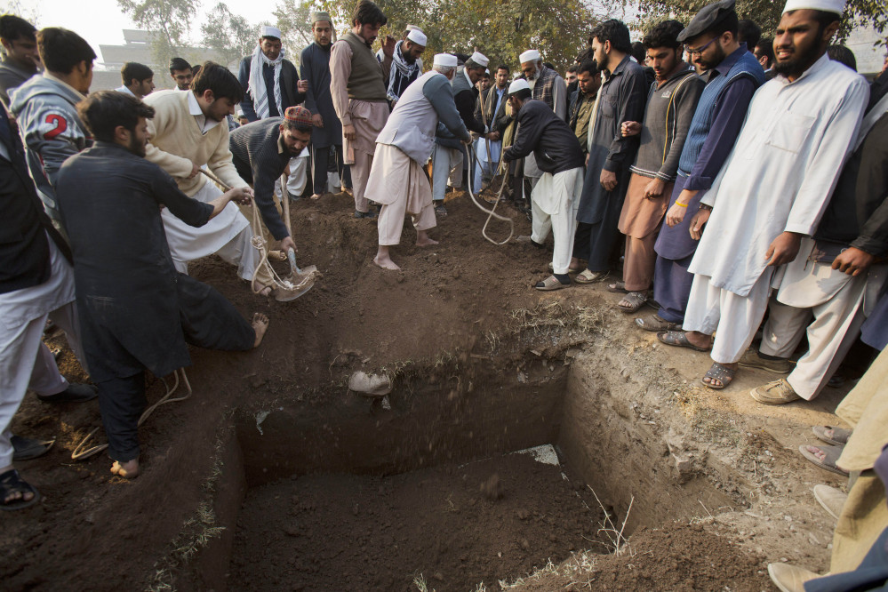 Pakistani villagers bury a body of the principal of the Army Public School that was attacked the day before by Taliban gunmen in Peshawar, Pakistan, Wednesday.
