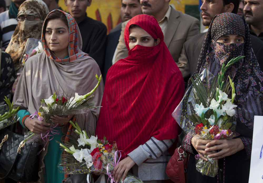 Pakistani women pay tribute to students and staff members killed in an attack by Taliban gunmen, as they gather outside the school in Peshawar on Wednesday.