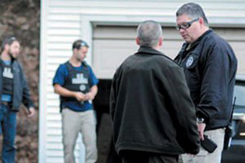 In this November 2012 file photo, U.S. Marshals Service investigators search the residence of Barbara Cameron, the ex-wife of James Cameron, in Hallowell. Authorities spent more than two weeks looking for Cameron in 2012 after he cut off his electronic monitoring bracelet and drove to New Mexico before being captured. Maine's former top drug prosecutor fled the state after learning his appeal of child pornography convictions had failed.