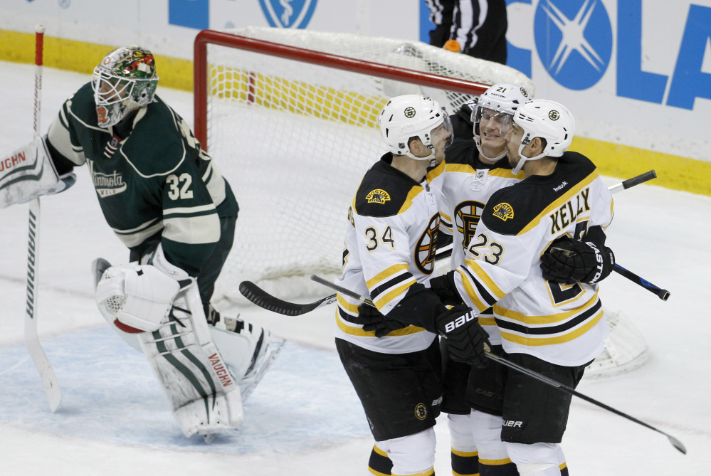 Boston's Chris Kelly (23) and Carl Soderberg (34) congratulate left wing Loui Eriksson after he scored the game-winning goal on Minnesota Wild goalie Niklas Backstrom in overtime Wednesday night in St. Paul, Minn.
