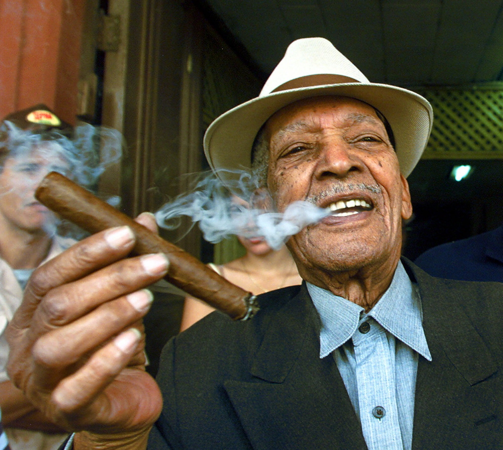 "Cuban singer Francisco Repilado ""Compay Segundo"", 94, smokes a cigar he rolled himself Thursday Feb. 22, 2001, in Havana, Cuba. Cigar aficionados from as far away as Israel and Hong Kong visited tobacco farms and factories and savored new cigar brands this week during an annual celebration of this nation's world-famous stogies. (AP Photo/Jose Goitia)"