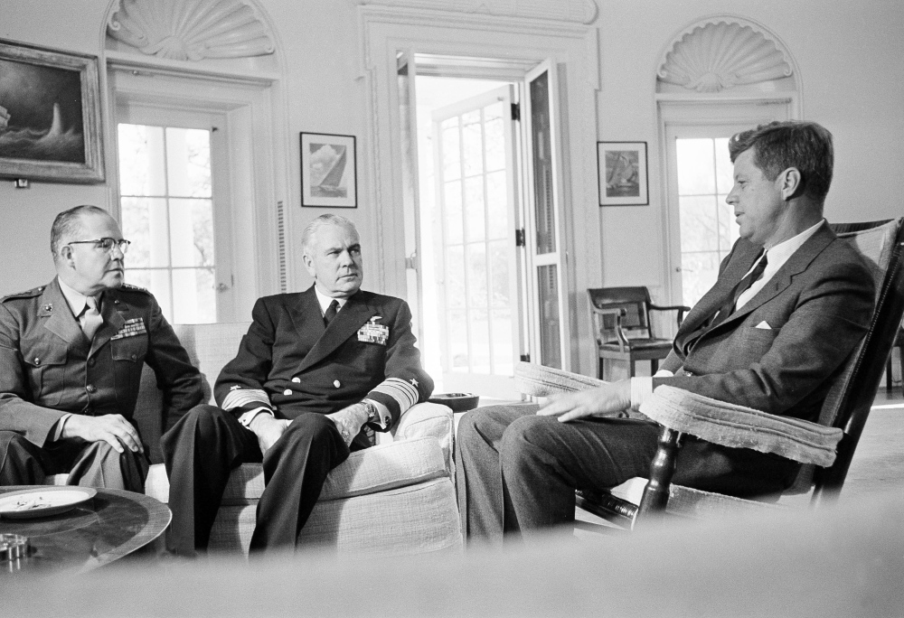 President John F. Kennedy poses in his White House office with Gen. David Shoup, left, Marine Corps Commandant, and Adm. George Anderson, Chief of U.S. Naval Operations, Oct. 29, 1962.  The chiefs met with the president to review the present situation in Cuba and operation of the U.S. naval blockade.  (AP Photo/William J. Smith)