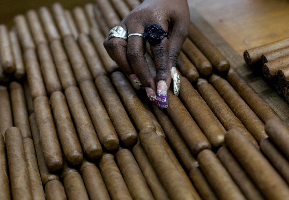 FILE - In this March 1, 2013 file photo, a worker selects cigars at the H. Upmann cigar factory, where people can take tours as part of the 15th annual Cigar Festival, in Havana, Cuba. Among those eager for access to a Cuban market cut off by an economic embargo are U.S. farmers, travel companies, energy producers and importers of rum and cigars. (AP Photo/Ramon Espinosa, File)