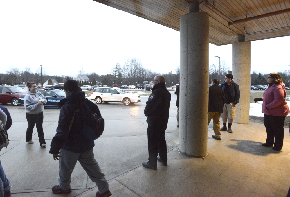 WINDHAM, ME - DECEMBER 18: Windham HS resource officer Jeff Smith (center) greets students as they and other students return to Windham schools after a threat canceled three days of classes. (Photo by John Patriquin/Staff Photographer)