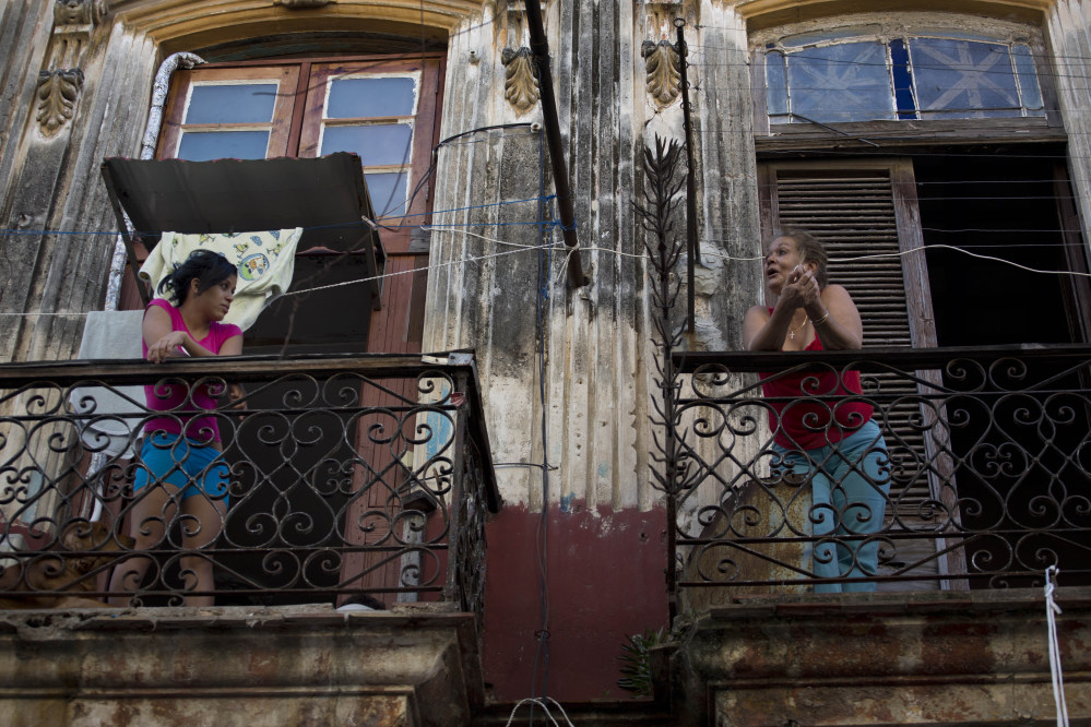 Two women talk across their balconies in Old Havana, Cuba, on Thursday. After a half-century of pointing fingers, a historic shift between the U.S. and Cuba could revitalize the flow of money and people between the two nations.