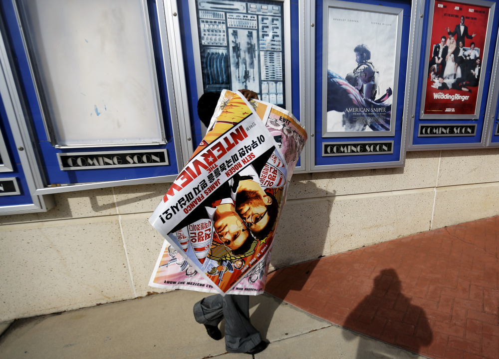 """A worker carries away a poster for the movie """"The Interview"""" after pulling it from a display case at a Carmike Cinemas movie theater in Atlanta on Wednesday."""