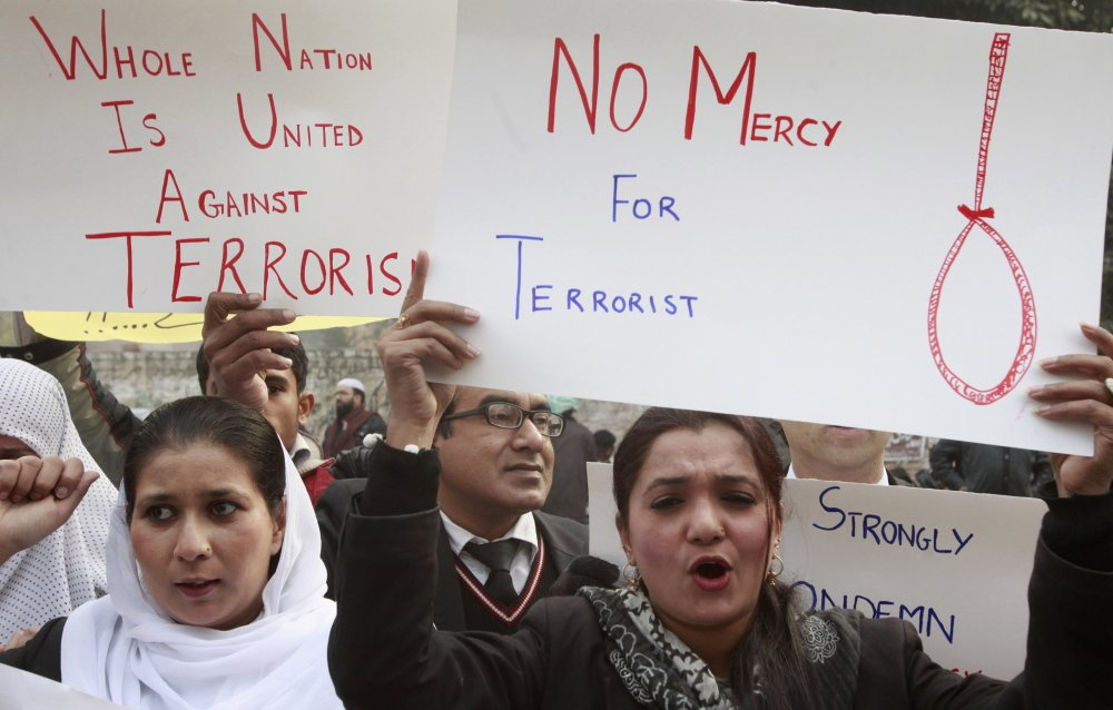 Civil society activists hold placards as they chant slogans condemning the attack on the Army Public School by Pakistan Taliban gunmen, during a rally in Lahore, Pakistan, on Thursday. The government and courts are moving toward executing convicted terrorists.