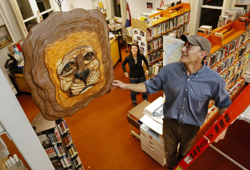 "Jack Soley, former chair of the Portland Public Art Committee, hangs ""Lion's Head"" at the Peaks Island branch library."